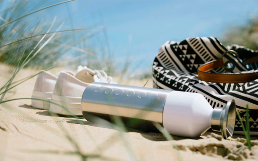 dutch dopper steel bottle laying in grassy sand dune next to beach bag and white canvas shoes