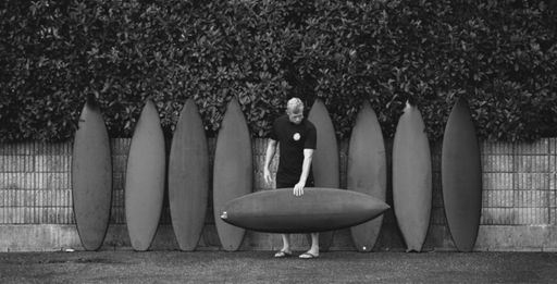 Man holding wooden surfboard one handed in front of row of wooden surfboards