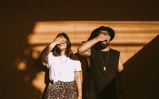 A man and woman in trendy clothing covering their eyes.