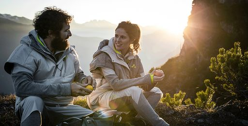 A bearded man and a pretty woman wearing Vaude outdoor gear and peeling fruit atop a mountain as sun sets in background