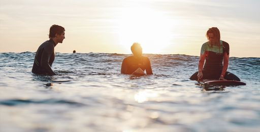 Three surfers wearing Picture Organic naturalprene wetsuits sitting on surfboards in calm water as sun sets in background
