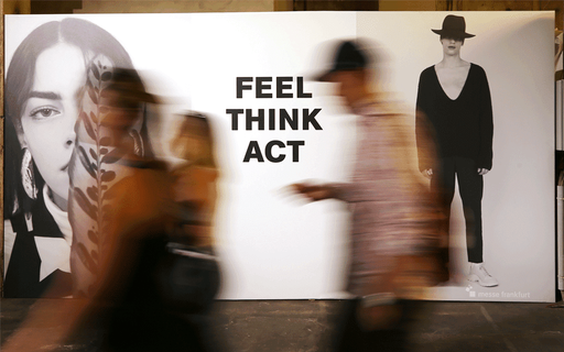 Advertising board with words FEEL THINK ACT emblazoned on it. A woman's face and the figure of a man are either side.
