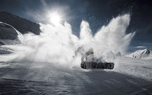 snowboarder ripping up the snow into a powder spray that partially secludes the sun