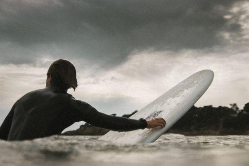 Man paddling inland. Grey clouds above.