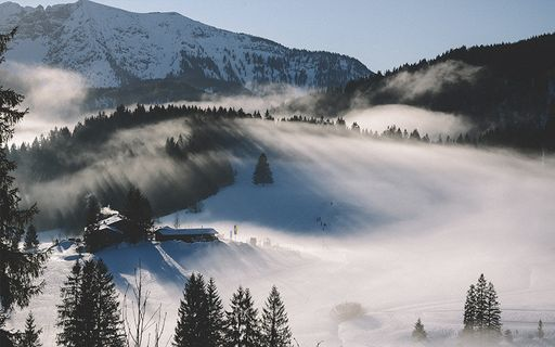Snowy mountain scene with a cottage, pine trees and fog.