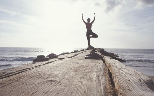 Man doing yoga pose at the end of a long, rustic wooden pier
