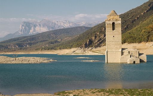 Stone tower in a shallow river against a green mountain and blue sky